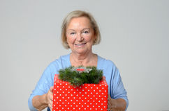 Attractive elderly lady with a large Xmas gift Royalty Free Stock Photography