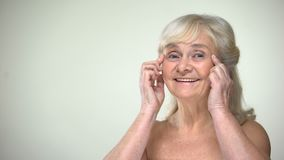 Attractive elderly lady unwrinkling, smiling to camera, aging beauty concept stock footage