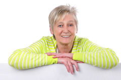 Attractive elderly woman behind a white board Stock Photo