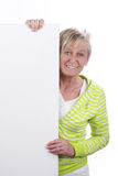 Attractive elderly woman behind a white board Stock Image