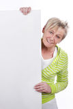 Attractive elderly woman behind a white board Royalty Free Stock Photo