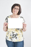 Attractive elderly woman holding a blank white sheet of paper fo Royalty Free Stock Photography