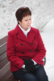 Attractive elderly woman sitting on bench on winter snowy street Stock Image