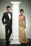 Attractive elegant couple posing near column in studio Stock Images