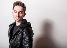 Attractive elegant man in stylish black leather jacket posing on light gray background.  Stock Images