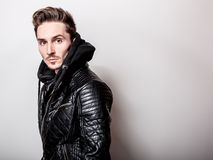 Attractive elegant man in stylish black leather jacket posing on light gray background.  Royalty Free Stock Image
