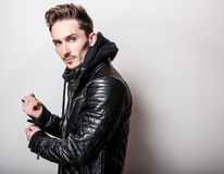 Attractive elegant man in stylish black leather jacket posing on light gray background royalty free stock image