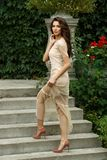 Attractive and elegant rich young lady in dress is posing on stairs of beautiful estate in park stock photos