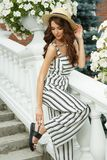Attractive and elegant rich young lady in hat is posing on stairs of beautiful mansion Royalty Free Stock Photo