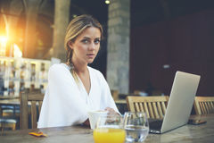Attractive elegant women sitting at the table with open laptop computer during morning breakfast. Portrait of a young pretty female freelancer using net-book for Royalty Free Stock Images
