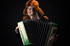 Attractive emotional woman in fur hat playing the accordion Stock Photo