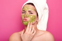 Attractive emotional young beauty has green mask on her face, day to have spa procedures, protrudes her lips, has unpleasant. Facial expression. Magnetic model royalty free stock photos