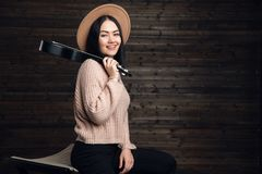 Attractive emotional young Caucasian woman in sweater and hat playing ukulele. Beautiful woman singer playing musical stock photos
