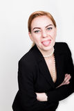 Attractive and energetic business woma in a suit on naked body showing tongue. Attractive and energetic business woma in a suit on a naked body showing tongue royalty free stock image