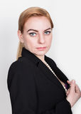 Attractive and energetic business woma in a suit on naked body smiling, holding pearls.  royalty free stock photography