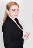 Attractive and energetic business woma in a suit on naked body smiling, holding pearls.  stock image