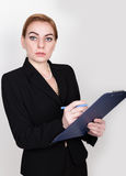 Attractive energetic business woman holding pad for writing and takes notes Stock Image