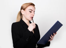 Attractive energetic business woman holding pad for writing and takes notes Stock Photography
