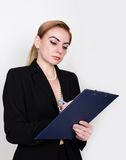 Attractive energetic business woman holding pad for writing and takes notes Royalty Free Stock Image