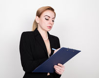 Attractive energetic business woman holding pad for writing and takes notes. Attractive and energetic business woman holding pad for writing and takes notes Royalty Free Stock Photos