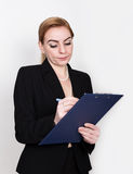 Attractive energetic business woman holding pad for writing and takes notes. Attractive and energetic business woman holding pad for writing and takes notes Stock Photography