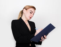 Attractive energetic business woman holding pad for writing and takes notes. Attractive and energetic business woman holding pad for writing and takes notes Royalty Free Stock Image