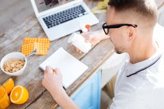 Attractive energetic man consuming biohacking supplements. Order in everything. Top view of bearded nice concentrated man writing down while trying to take royalty free stock photography