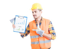 Attractive engineer pointing finger to a paper with sales chart Stock Image