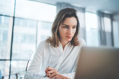 Attractive entrepreneur female using mobile laptop for looking a new business solution during work process at office royalty free stock images