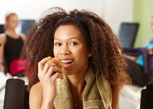 Attractive ethnic girl eating apple at gym Stock Photo