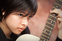 Attractive Ethnic Girl Plays Guitar Stock Photo