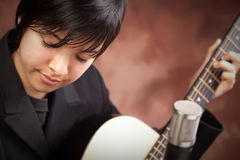 Attractive Ethnic Girl Plays Guitar Royalty Free Stock Image