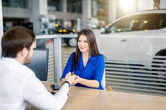 Attractive european woman receiving car keys from car sales agent. Attractive european business lady receiving car keys from car sales agent at car dealership royalty free stock image