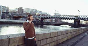 Attractive European businessman using smart phone in front of Drogheda City. Handsome young businessman communicating on stock video
