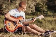 Attractive European male teenager sits on grass, plays acoustic guitar, recreats during summer day, practices new song, sings, enj. Oy calm atmosphere outside Stock Photography