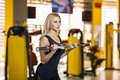 Sportswoman coaches the biceps of hands, lifting a metal w-bar, in the gym. An attractive European sportswoman, a blonde with long hair, is dressed in a black Stock Photo