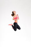 Attractive excited fitness girl in sportwear jumping of joy. Isolated over white background Royalty Free Stock Images