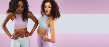 Two fitness women in sportswear isolated over gray background. Sport and fashion concept wit chopy space. Royalty Free Stock Photo