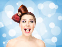Attractive excited girl with colored hair having candy in mouth on bubbly background Royalty Free Stock Images