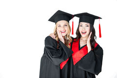 Attractive excited students in graduation caps hugging isolated Royalty Free Stock Image