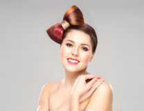 Attractive excited woman with a bow haircut and colorful make-up on grey background Stock Photos