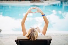 Attractive excited young woman with raised hands make heart enjoying summer vacation near pool. Attractive excited woman with raised hands make heart enjoying Royalty Free Stock Photo