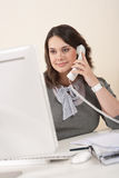 Attractive executive woman on phone at office Royalty Free Stock Photo