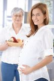Attractive expectant mother smiling happily Stock Photos