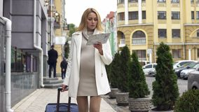 Attractive expecting female with suitcase looking for clinic in city, travel stock photography