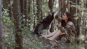 Attractive fair-skinned young woman sitting and playing with her husky dog. Attractive fair-skinned young woman sitting in beautiful dense forest and playing stock footage