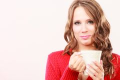 Autumn woman holds mug with coffee warm beverage. Attractive fall girl long hair red autumnal sweater holding white mug with coffee warm beverage. Woman warming Royalty Free Stock Photo