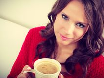 Autumn woman holds mug with coffee sitting on sofa Stock Photography