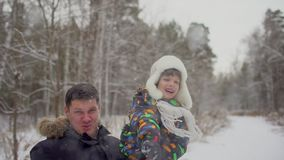 Attractive family having fun in a snow winter park. Cute little boy throws snowball. Father and son playing outside on stock video footage