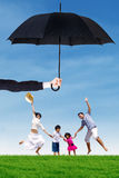 Attractive family jumping at field under umbrella. Joyful family jumping on the meadow while holding hands under umbrella. Life and family insurance concept Stock Photos
